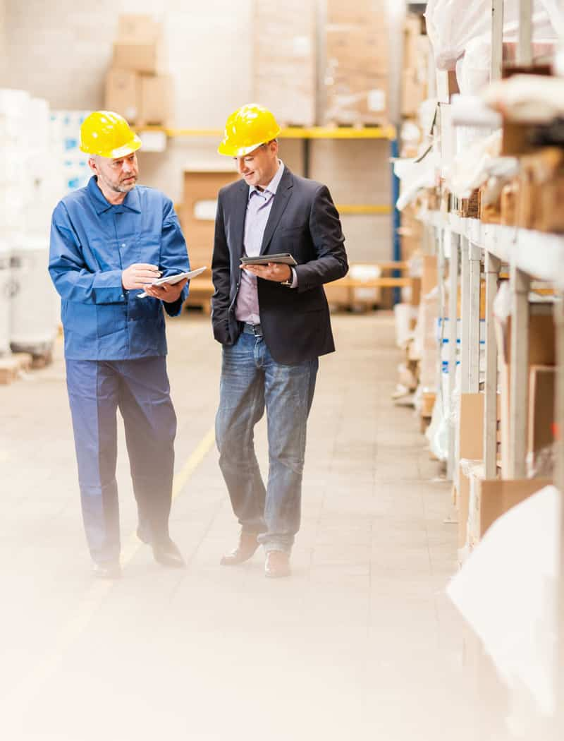 Manager talking with employee in a warehouse.